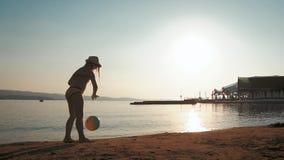 Gioco della bambina con la palla variopinta sulla spiaggia al tramonto Godere di una vacanza adorabile archivi video