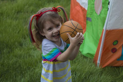 Gioco della bambina con la sfera nella sosta Immagini Stock