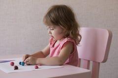 Gioco della bambina con plasticine a casa Immagini Stock