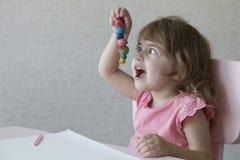 Gioco della bambina con plasticine a casa Fotografia Stock