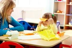 Gioco della bambina e dell'insegnante con il documento di colore Immagine Stock