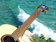 Gioco della chitarra che osserva il mare Immagini Stock