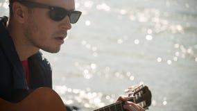 Gioco della chitarra sui precedenti di abbagliamento dall'acqua Immagine Stock Libera da Diritti