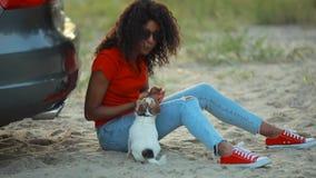 Gioco della donna con il suo cane che si siede vicino all'automobile archivi video