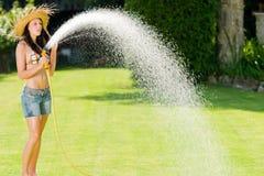 Gioco della donna del giardino di estate con il tubo flessibile dell'acqua fotografia stock