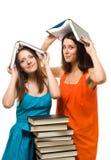Gioco della donna dell'allievo dei due giovani con i libri Fotografie Stock Libere da Diritti