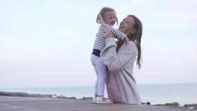 Gioco della figlia e della mamma sul lungomare dal mare stock footage