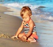 Gioco della neonata su una spiaggia di sabbia Fotografia Stock Libera da Diritti