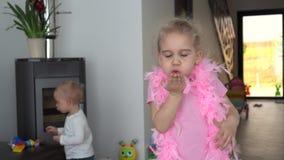 Gioco della ragazza del bambino con lo scialle ed il ragazzo rosa della piuma a casa Colpo del giunto cardanico stock footage