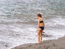 Gioco della ragazza su una spiaggia nelle onde del mare e giocare sulla spiaggia di sabbia vulcanica immagine stock
