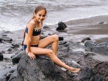 Gioco della ragazza su una spiaggia nelle onde del mare e giocare sulla spiaggia di sabbia vulcanica fotografie stock