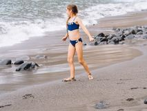 Gioco della ragazza su una spiaggia nelle onde del mare e giocare sulla spiaggia di sabbia vulcanica fotografia stock