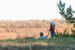 Gioco della sorella e del fratello insieme nell'erba nei fiori asciutti dello strappo della foresta Fotografie Stock Libere da Diritti