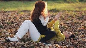 Gioco delle mani della figlia e della mamma Essi che giocano sulle foglie cadute Famiglia felice nella sosta di autunno archivi video