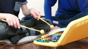Gioco dello strumento di musica Il ` s del ragazzo del primo piano passa il gioco sullo xilofono con i bastoni e sulla sua mamma  stock footage