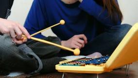 Gioco dello strumento di musica Mano del ` s del ragazzo del primo piano che giocano sullo xilofono e la sua mamma che si siede v video d archivio