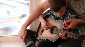 Gioco dello strumento musicale Il papà insegna a suo figlio a giocare la chitarra, sedentesi sul davanzale video d archivio