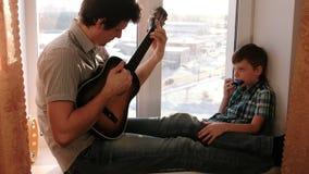 Gioco dello strumento musicale Il papà sta giocando la chitarra ed il figlio sta giocando l'armonica a bocca che si siede nel dav video d archivio