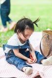 Gioco di 2 anni della neonata sveglia sulla coperta di picnic Immagini Stock