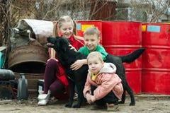 Gioco di bambini allo scarico con il cane Immagini Stock Libere da Diritti