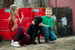 Gioco di bambini allo scarico con il cane Fotografie Stock Libere da Diritti