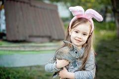 Gioco di bambini con coniglio reale Il bambino di risata all'uovo di Pasqua cerca con il coniglietto bianco dell'animale domestic Immagine Stock