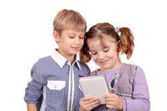 Gioco di bambini con la compressa Fotografie Stock