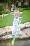 Gioco di bambini nel giardino con i waterguns fotografie stock libere da diritti