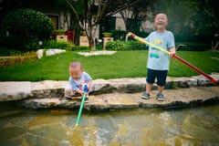 Gioco di bambini nel giardino con le pistole ed i fucili dell'acqua fotografia stock