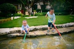 Gioco di bambini nel giardino con le pistole ed i fucili dell'acqua fotografie stock