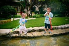 Gioco di bambini nel giardino con le pistole ed i fucili dell'acqua immagini stock libere da diritti