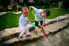 Gioco di bambini nel giardino con le pistole ed i fucili dell'acqua fotografia stock libera da diritti