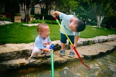 Gioco di bambini nel giardino con le pistole ed i fucili dell'acqua immagine stock