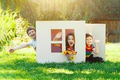 Gioco di bambini nella casa fatta della scatola di cartone Fotografia Stock