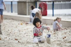 Gioco di bambini nella sabbia alla banca del sud di Tamigi nell'ora legale fotografia stock