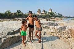 Gioco di bambini sulle pietre della sponda del fiume Immagini Stock