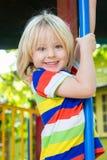 Gioco di bambino felice e sorridente in una terra del gioco Fotografie Stock Libere da Diritti