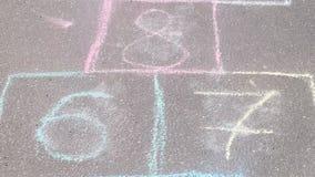 Gioco di campane su asfalto in parco Dipinto con i gessi variopinti archivi video