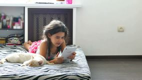 Gioco di gioco teenager di Internet della compressa della ragazza che si siede sul letto accanto al gatto video d archivio
