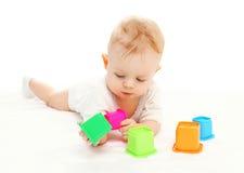 Gioco di menzogne del bambino con i giocattoli variopinti su bianco Fotografie Stock Libere da Diritti