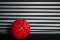 Gioco di pallacanestro: palla su un fondo a strisce della parete fotografia stock