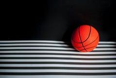 Gioco di pallacanestro: una palla arancio su un fondo scuro immagine stock