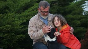 Gioco di prima generazione e del nipote con il loro cane in bianco e nero Fine settimana felice della famiglia Il bambino sta ind stock footage
