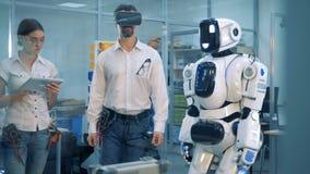Gioco di realtà virtuale Due ingegneri esaminano il lavoro del ` s del robot archivi video