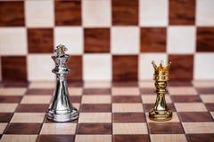 Gioco di scacchi Piccolo pegno che indossa il supporto dorato della corona per confrontare il re Affare competitivo e sfidare fotografia stock