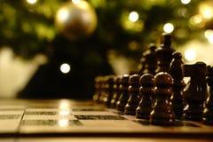 Gioco di scacchi vicino all'albero di Natale fotografie stock