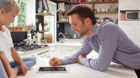 Gioco di And Son Playing del padre sulla compressa di Digital in cucina video d archivio
