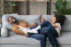Gioco divertente di risata del padre con la figlia che si trova sul sofà fotografia stock libera da diritti