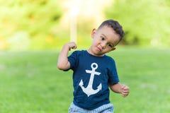Gioco e funzionamento adorabili del ragazzo in un parco all'aperto fotografia stock