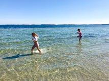 Gioco felice dei bambini allegro su una spiaggia in mare fotografia stock